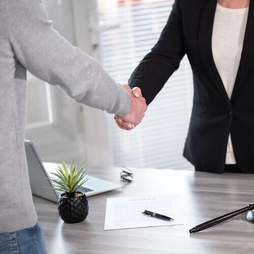 不動産売却の交渉が成立して握手するスタッフ