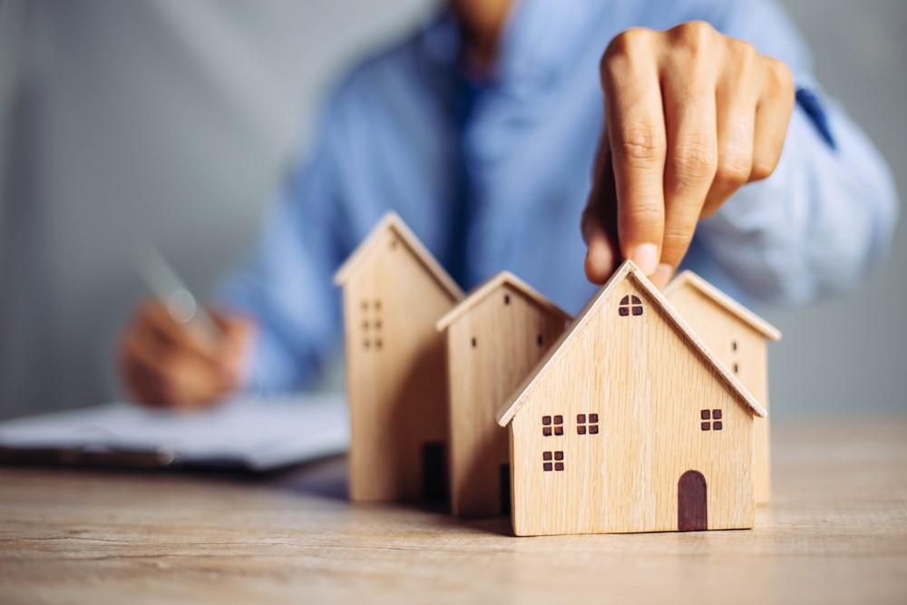 家の模型を摘まむ男性